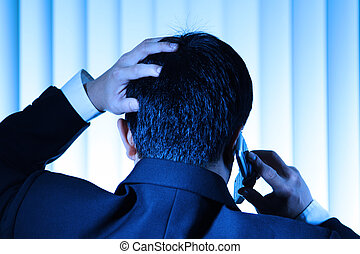 Stress - A stressed businessman talking on the phone in blue...