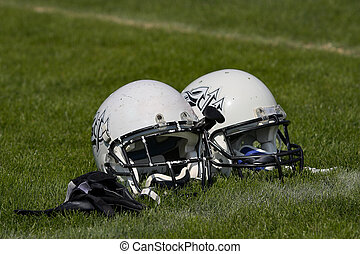 Football helmets - Two football helmets placed side by side...