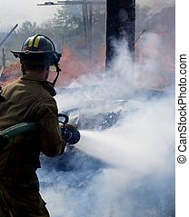 Putting out the fire - A firefighter wetting down hotspots...