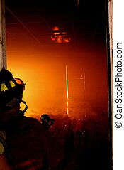 Facing the Beast - A firefighter looks at the flames across...