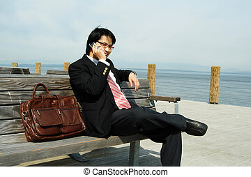 Businessman - A businessman talking on a cell phone outdoor