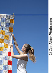 Young woman and bright laundry - Young woman touching a...