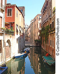 Gondola and small boats on a small water canal, Venice,...