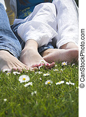 happy feet - couple showing their feet on grass with flowers