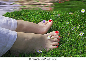 happy feet near water - woman feet on grass near water with...
