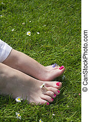 happy feet - woman feet on grass with flowers around
