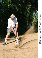 Sand Trap - A golfer hitting a ball in the sand trap