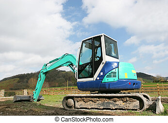 Mini Digger - Mini digger standing idle on rough ground in...