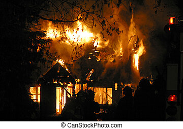 house fire - Firefighters are silhouetted by a blazing house...