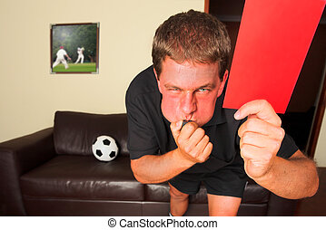 Referee in sitting room blowing whistle with red card - A...