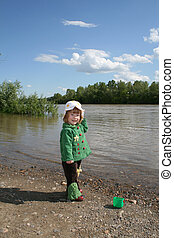 The girl ashore of river - Small girl in green plays ashore...
