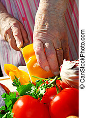 Cutting vegetables - Hands of an elderly woman cutting fresh...