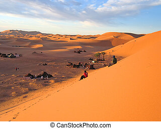Red and brown sand dunes with people watching the sunset,...