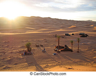 Sunset on the dunes with camels having some rest in the tent...