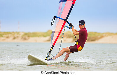 Windsurfer 27 - Fast moving windsurfer on the water at...