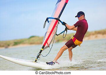windsurfer 28 - Fast moving windsurfer on the water at...