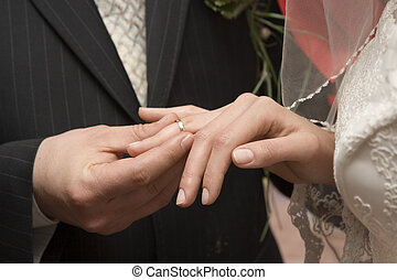 wedding ring - The groom puts on a wedding ring to finger of...