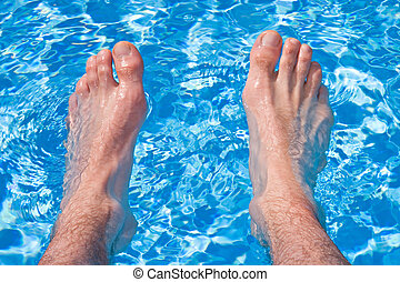 Holliday Relaxation on Pool - Men feet in transparent water