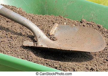 Gardening-Shovel-Sandy Soil-Wheelbarrow - A shovel rests on...