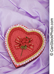 Heart shaped box of candy laying on satin
