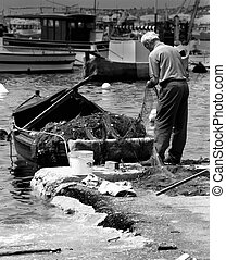 Mending the Nets - Old fisherman fixing his nets at the...