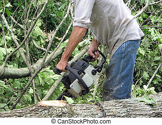chainsaw stance - man standing in proper position cutting...