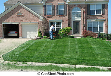 Mowing The Lawn - Professional lawn care; a worker using a...
