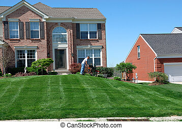 Mowing The Lawn - Professional lawn care service using a...