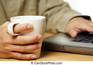 Businessman - A businessman holding a cup of coffee while...