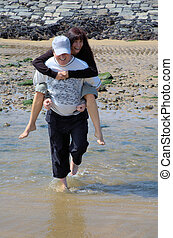 No wet feet, please - Man carrying his wife over a puddle by...