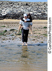 No wet feet please - Man carrying his wife over a puddle