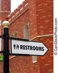 Restroom direction sign in front of old brick building