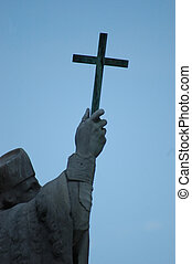 Cross in hand of a statue as a symbol of christianity