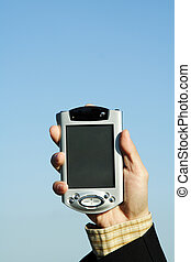 Businessman with PDA - An image of a businessman holding up...