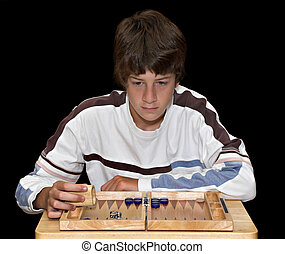 Boy playing Backgammon - A young teenage boy playing a game...
