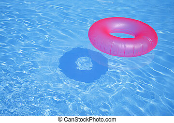 Pink Inflatable Ring - Pink inflatable ring in blue swimming...