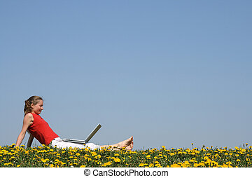 Young woman relaxing with laptop outdoors