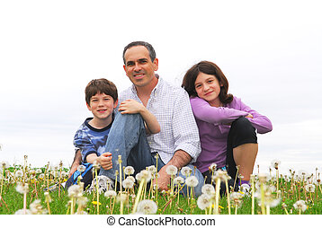 Happy family - Portrait of a happy family of three on green...
