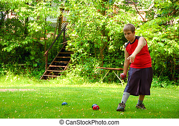 Child Playing Bocce Ball - A young child playing bocce ball