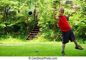 Throwing the Bocce Ball - A young boy throwing the bocce...