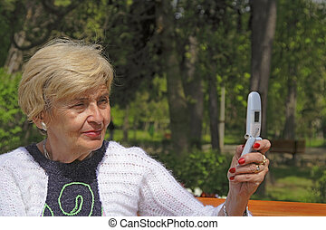Senior woman with camera phone - Senior woman using a mobile...