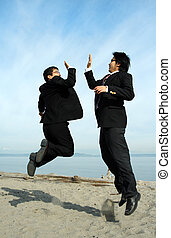 Happy businessmen - Two businessmen jumping happily on the...