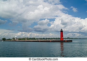 Red lighthouse under dramatic blue and white sky in Kenosha,...