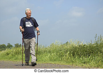 Walking Senior - Senior man doing a Nordic Walk on a sunny...
