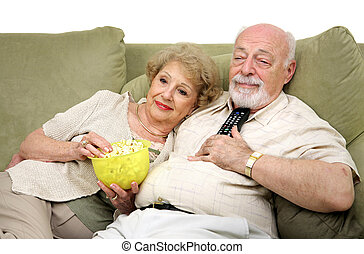 Relaxing With Television - A senior couple relaxing and...