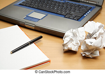 Business planning - A laptop and a notebook with crumpled...