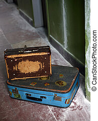 Two old suitcases on a dirty floor
