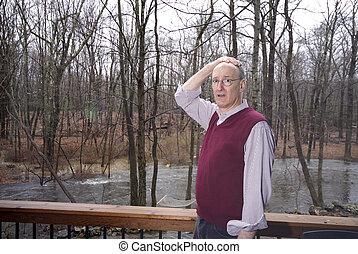 looking at flooded backyard - suburban man looking at...