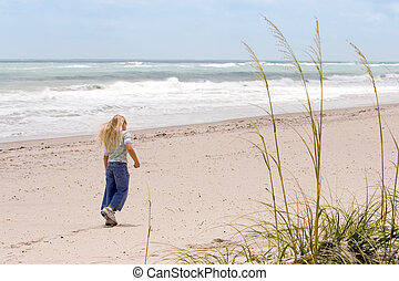 Beach walk - Young girl walking on the beach with Sea Oats...