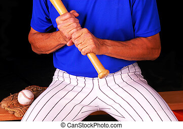 Baseball Player - Baseball player sitting on bench with bat...